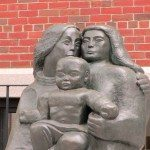 Metal sculpture of family.