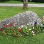Large rock with flowers of red, white, and blue decorated for summer