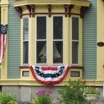 Captain's house on main street with a flag hanging by the window, ship seen through the curtain.