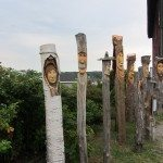 Eight wooden sculptures lined up with various female, male faces.