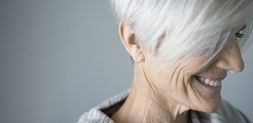 Close up portrait smiling senior woman looking down